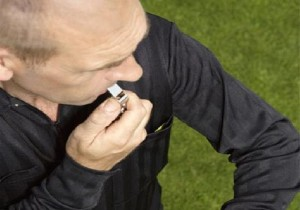 Soccer Referee Blowing Whistle and Looking at Watch